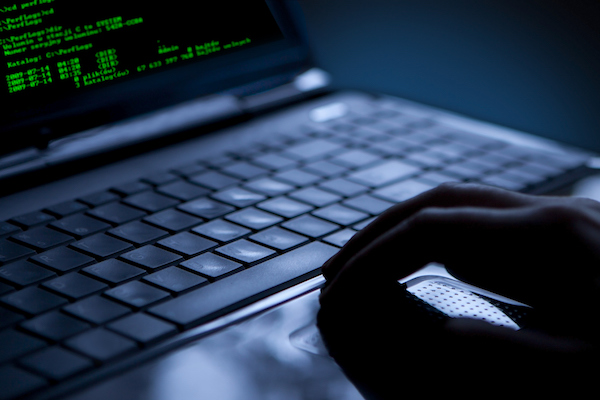 image of a hacker using a laptop for a blog about are you ready for ransomware by MTI